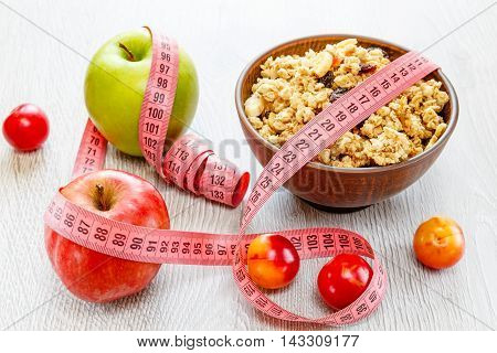 Beautiful plate with muesli plums apple and meter tape