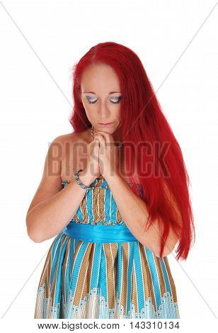 A woman in her thirties with long red hair holding her hands and praying isolated for white background.