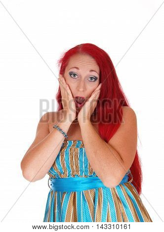 A pretty woman in her thirties with long red hair holding her face is shocked what she sees isolated for white background.