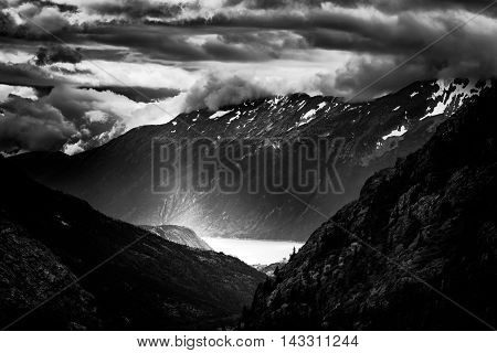 Ominous clouds over snow-capped mountains and a Pacific Ocean bay near Skagway Alaska