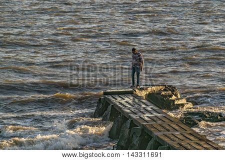 MONTEVIDEO, URUGUAY, DECEMBER - 2015 - Backlighting scene of young man standing at breakwater on river plate river in Montevideo Uruguay