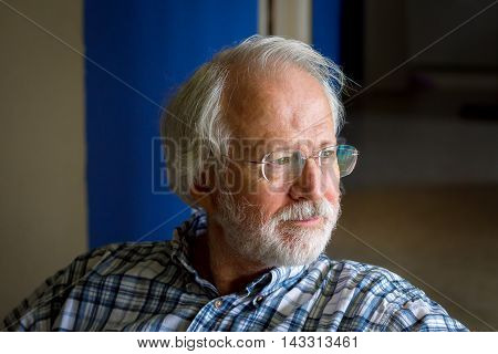 A senior man with white hair mustache beard and glasses looks contemplative as he stares out a window. His face is lit by the window light.