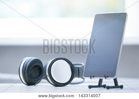 Horizontal photo of headphones and digital tablet at office