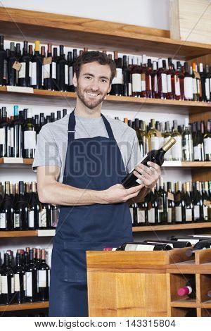 Portrait Of Salesman Holding Wine Bottle