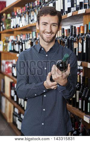 Male Customer Holding Wine Bottle By Shelves