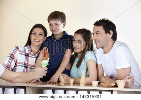 Family Looking At Waiter Giving Ice Cream At Counter