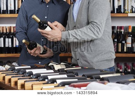 Midsection Of Friends Holding Wine Bottles At Table Rack