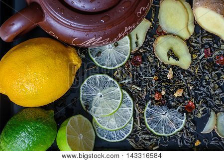 teapot with ingredients for ginger tea beverage with lime recipe helpful for colds.