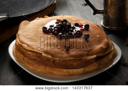 Breakfast in the rustic style: lots of freshly cooked crepes or pancakes, top watered with jam and decorated with berries. Against the background panand a frying pan.