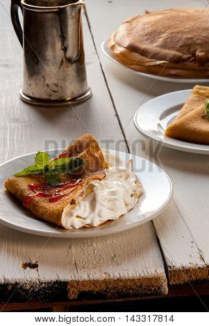 A light breakfast or lunch, with pancakes (crepes) and whipped cream. On the table is the coffee. Sunny morning, white wooden table