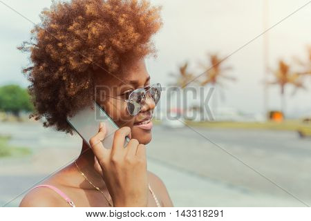Happy beautiful african american young woman calling on smartphone, ocean beach in the background