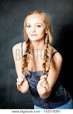 Young Beautiful Girl with Blond Braids. Natural Makeup and Fashion Hairstyle