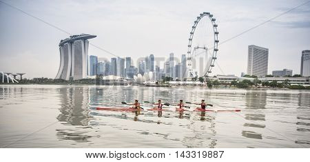 SINGAPORE - APRIL 22: Four young women rowing on a river on April 22 2015 in Singapore.
