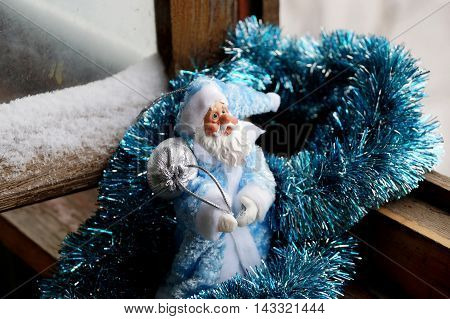 Toy Father Frost in a blue fur coat with a silvery bag