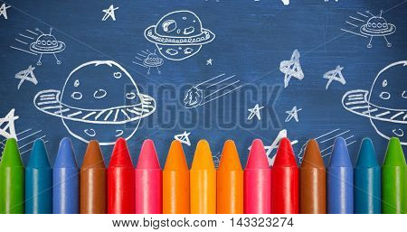 Colourful crayons against blue chalkboard