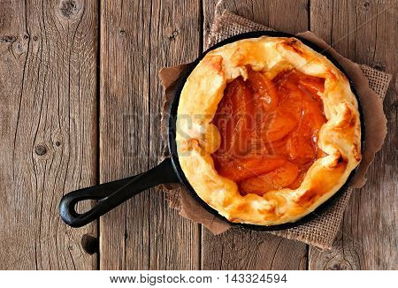 Rustic Peach Tart In Cast Iron Baking Skillet On A Old Wood Background