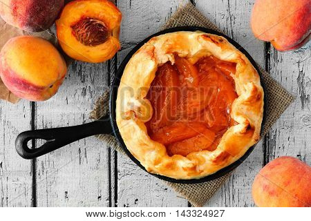 Rustic Peach Tart In Cast Iron Baking Skillet, Overhead Scene On White Wood
