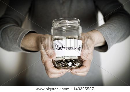 Retirement concept with hands holding a money jar