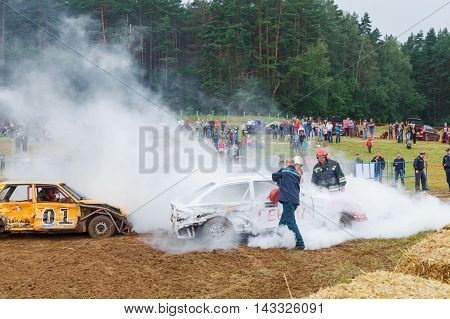 GRODNO BELARUS - AUG 13: Firefighters extinguish a car on Car fighting for survival on August 13 2016 in Grodno Belarus