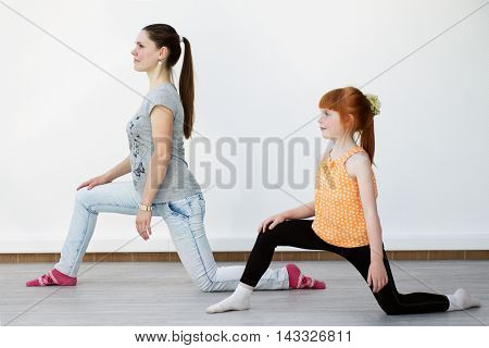 Mother and daughter are training together at the gym