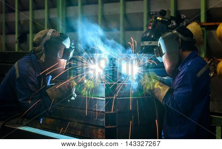 Worker welding the steel part in factory