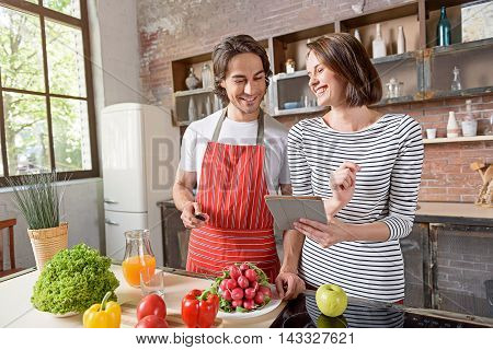 Lets cook this dish. Happy young woman is holding tablet and showing recipe to husband. Man is standing in kitchen and holding knife. They are laughing