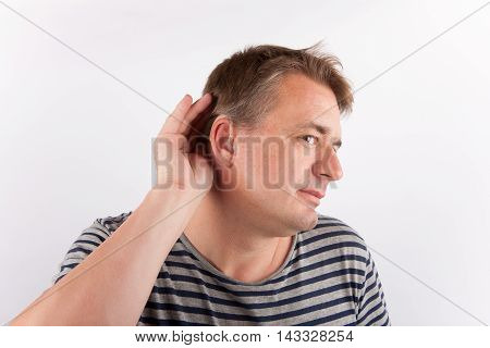 Senior man wearing hearing aid cupping his ear having difficulty hearing