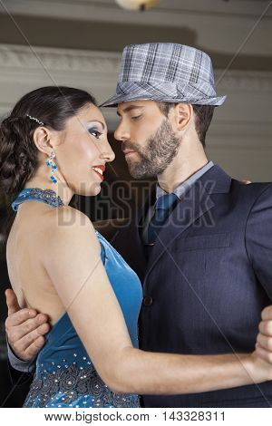 Welldressed Dancers Performing Tango In Cafe