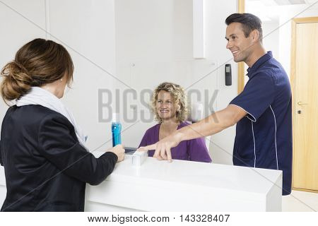 Dentists Giving Medicines To Patient At Reception Desk