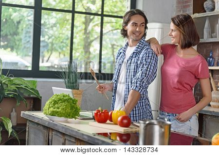 Joyful husband and wife are ready to cook something delicious. They are standing near laptop in kitchen and smiling