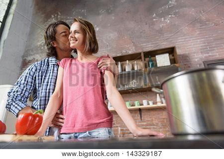 Happy married couple is preparing food in kitchen. Man is standing and kissing his wife with love. Woman is smiling