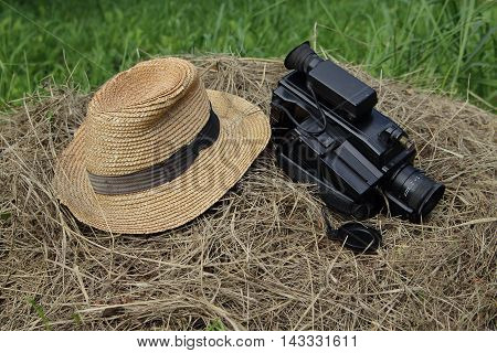 Old hat and video camera on a haystack in a garden