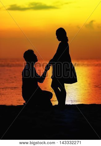 Pregnant couple sunset silhouette at the beach