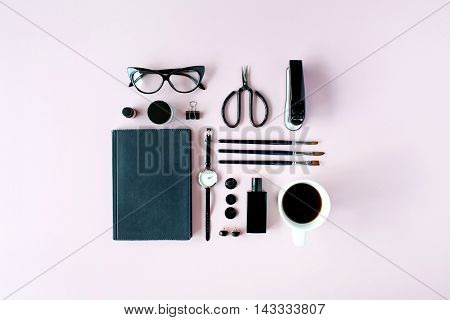 Flat lay top view black style office table desk. feminine working supplies: glasses diary watches perfume brushes scissors coffee on pink background.