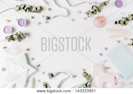 floral frame with rose buds dry eucalyptus branches candles ribbon and buttons on white background. flat lay top view
