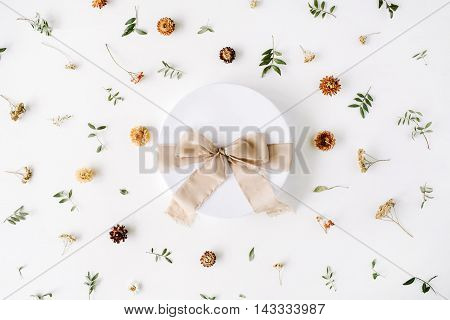 white gift cardboard box with brown bow on white background with floral composition. flat lat top view