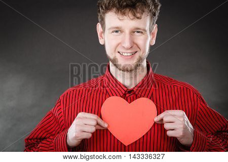 Love and help from people. Charming lovely man with red paper heart persuade to be good helpful hopeful. Valentines Day or charity concept.