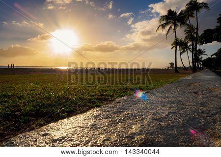 Honolulu, Hawaii, USA - Dec 21, 2015: Setting sun over beach at Ala Moana Park, along Ala Moana Park Drive. The beach overlooks Mamala Bay and features some flares.