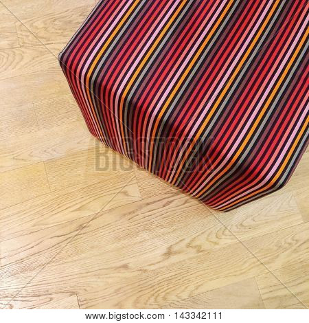 Colorful striped cube chair on wooden floor. Modern design furniture.