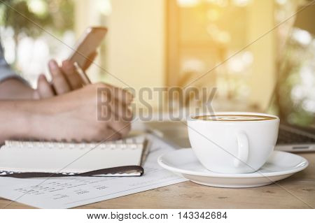 Business man using smartphone and laptop analysis document chart