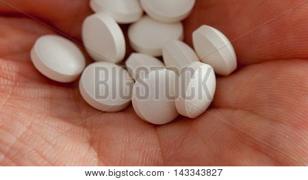 Pills On Hand Close-up Isolated On White