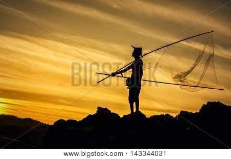 Beautiful sunset in countryside of Thailand with the silhouette of a fisherman