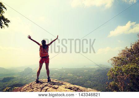 cheering woman hiker open arms on mountain peak