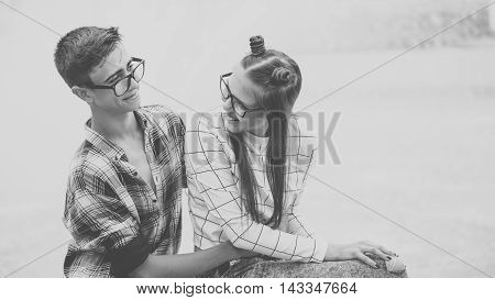 Loving couple teenagers hug. Girlfriend and boyfriend hugging. They wear glasses. Black and white photography. First love. He falls in love. Date.