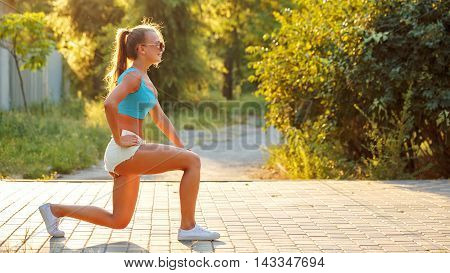 Young slim woman doing lunges in a city park. Outdoors Sports. Healthy lifestyle concept. Morning exercises