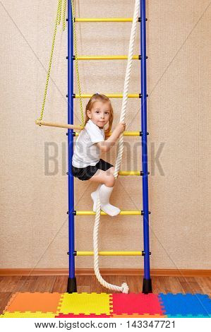 Little girl climbs the stairs holding on to the rope. Wall bars. Sports Equipment. Children's sports.