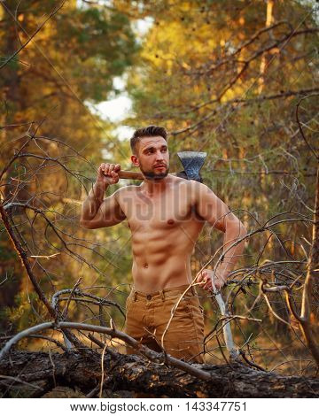 Lumberjack with an ax resting on his shoulder. Woodcutter with naked torso in the coniferous forest. Felling trees. Logging. Manual labor. Brutal man.