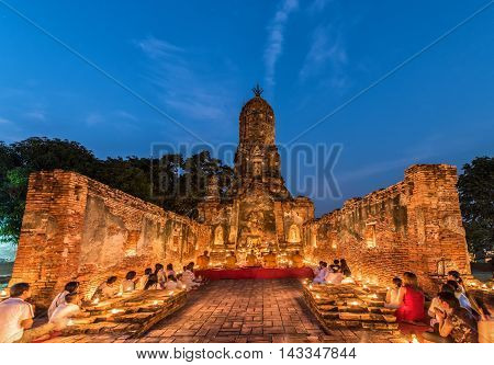 Ayutthaya Thailand - February 22 2016: People praying respect to monk on Ayutthaya. Roughly 95% of the Thai people are practitioners of Theravada Buddhism the official religion of Thailand