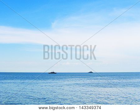 Two vessels looked small at horizon between blue sky and ocean