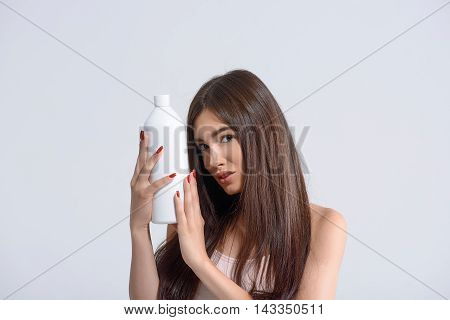 Young woman with perfect smooth hair is showing bottle of shampoo. She is standing and looking at camera confidently. Isolated